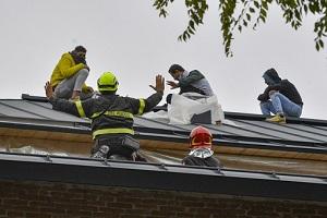 Operai salgono su un tetto per protesta